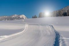 Puesta del sol hermosa sobre el camino nevoso Foto de archivo