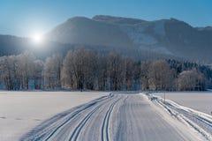 Puesta del sol hermosa sobre el camino nevoso Imágenes de archivo libres de regalías