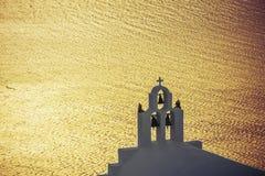 Puesta del sol hermosa sobre el campanario en la isla de Santorini foto de archivo libre de regalías
