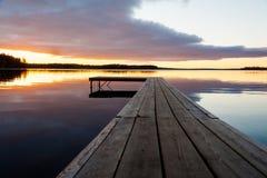 Puesta del sol hermosa sobre el embarcadero de la madera Fotos de archivo