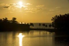 Puesta del sol hermosa sobre el hotel en las orillas del océano Foto de archivo