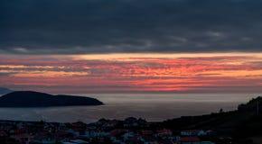 Puesta del sol hermosa sobre la ciudad por el mar fotos de archivo libres de regalías
