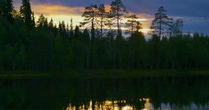 Puesta del sol hermosa sobre un lago en el bosque finlandés almacen de metraje de vídeo