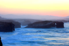 Puesta del sol hermosa y arcos de piedra en Playa de las Catedrales Imagen de archivo libre de regalías