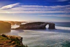 Puesta del sol hermosa y arcos de piedra en Playa de las Catedrales Fotos de archivo