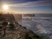 Puesta del sol hermosa y arcos de piedra en Playa de las Catedrales Foto de archivo