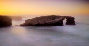 Puesta del sol hermosa y arcos de piedra en Playa de las Catedrales, España Imágenes de archivo libres de regalías