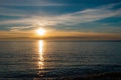 Puesta del sol hermosa y brillante en la costa de mar en tonos azules y amarillos fotos de archivo