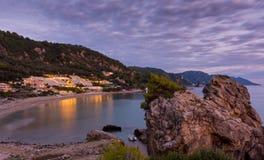 Puesta del sol hermosa y una roca grande con los árboles en el top en la costa de Corfú central Grecia Imágenes de archivo libres de regalías