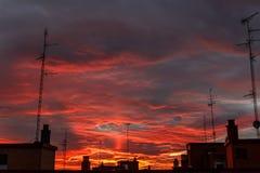 Puesta del sol imponente sobre una ciudad, rica en las nubes oscuras, rayos de la luz Imagen de archivo libre de regalías