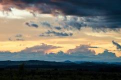 Puesta del sol impresionante con las nubes de tormenta que se elevan en distancia imagen de archivo