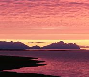 Puesta del sol increíblemente hermosa del amanecer en la orilla del Océano Atlántico Siluetas de montañas y de nubes rojas Imágenes de archivo libres de regalías