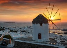 Puesta del sol intensa detrás del molino de viento famoso y de la ciudad de la isla de Mykonos Fotografía de archivo