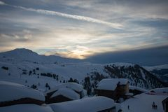 Puesta del sol del invierno en un villlage nevado de la montaña Imágenes de archivo libres de regalías