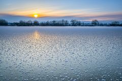 Puesta del sol del invierno sobre el lago congelado en Colorado Imágenes de archivo libres de regalías