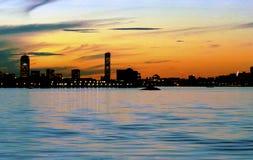 Puesta del sol luminosa sobre el puerto del sur de Boston con el horizonte y los edificios prudenciales y de Hancock Foto de archivo libre de regalías