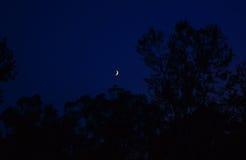 Puesta del sol mágica con las nubes y la luna coloridas fotografía de archivo libre de regalías