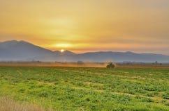 Puesta del sol - máquina rural que trabaja en el campo de la agricultura Imagen de archivo