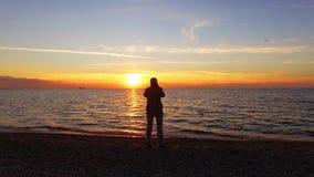 Puesta del sol m?gica de Taking Picture Of del fot?grafo en la playa metrajes