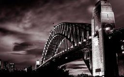 Puesta del sol magnífica en el puente de acero poderoso de Sydney Harbor que cruza el océano imagen de archivo