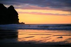 Puesta del sol magnífica en la playa de Piha Foto de archivo libre de regalías