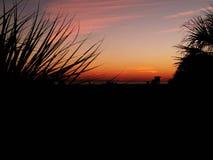 Puesta del sol magnífica en una playa arenosa blanca debajo de un cielo nublado con las nubes mullidas blancas imagen de archivo libre de regalías