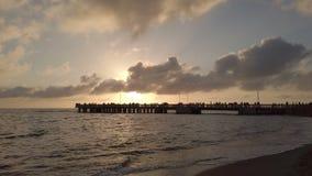 Puesta del sol del mar con reflejos de luz y la silueta de la gente en el embarcadero metrajes