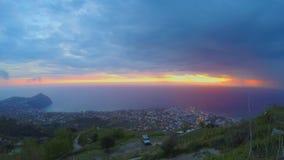Puesta del sol maravillosa del océano, opinión sobre ciudad del pico de montaña, timelapse pesado de las nubes almacen de video