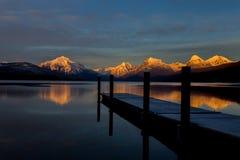 Puesta del sol, montañas, reflexión, lago, muelle Fotos de archivo libres de regalías
