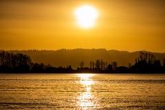 Puesta del sol nebulosa sobre el río Columbia con la reflexión fotos de archivo