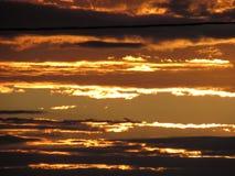 Puesta del sol nubes anaranjadas paralelas Fotos de archivo