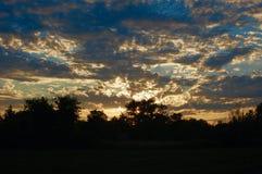 Puesta del sol nublada con el cielo azul sobre tierras de labrantío en Ontario, Canadá imagen de archivo