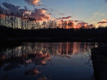 Puesta del sol nublada de la reflexión Foto de archivo