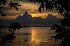 Puesta del sol nublada en el lago Imagen de archivo