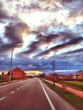 Puesta del sol nublada sobre la calle Imagenes de archivo