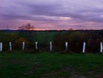 Puesta del sol nublada a través de los campos en invierno fotografía de archivo libre de regalías