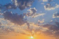 Puesta del sol o salida del sol hermosa con el sol y las nubes anaranjadas, grises en el cielo azul Foto de archivo libre de regalías