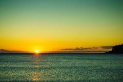 Puesta del sol o salida del sol sobre superficie del mar Foto de archivo libre de regalías