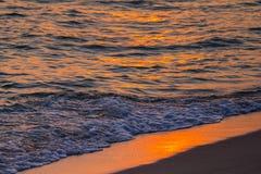 Puesta del sol, onda y arena Imagen de archivo libre de regalías