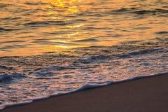 Puesta del sol, onda y arena Imágenes de archivo libres de regalías