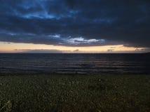 Puesta del sol oscura en el mar Imagen de archivo libre de regalías