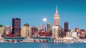 Puesta del sol, oscuridad y noche con una luna estupenda que sube sobre el horizonte de Nueva York almacen de metraje de vídeo