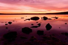 Puesta del sol púrpura sobre el agua del océano imagen de archivo