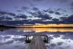 Puesta del sol púrpura sobre el embarcadero de madera en el lago tranquilo fotos de archivo libres de regalías