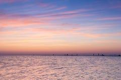Puesta del sol púrpura sobre el escupitajo de la arena en el mar Imágenes de archivo libres de regalías