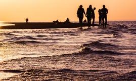 Puesta del sol púrpura sobre el escupitajo de la arena en el mar Imagen de archivo libre de regalías
