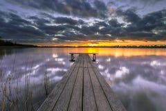 Puesta del sol púrpura sobre el lago tranquilo con el embarcadero de madera fotos de archivo