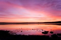 Puesta del sol púrpura sobre la agua de mar imágenes de archivo libres de regalías