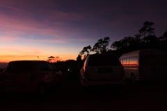 Puesta del sol púrpura viva espectacular y coche silueteados imagenes de archivo