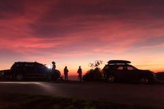 Puesta del sol púrpura viva espectacular y coche silueteados foto de archivo